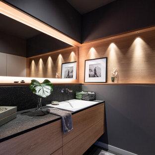 Exemple d'une grand salle d'eau tendance en bois avec un mur noir, un sol en carrelage de céramique, un lavabo posé, un plan de toilette en granite, un sol gris, meuble-lavabo suspendu, un placard à porte plane, des portes de placard en bois brun et un plan de toilette noir.