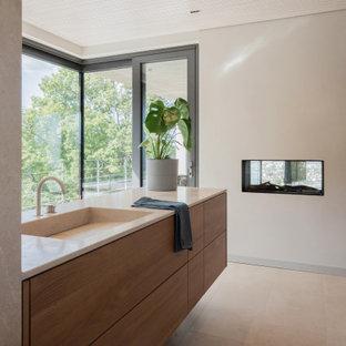 Idéer för ett stort modernt beige badrum med dusch, med släta luckor, beige skåp, ett platsbyggt badkar, en dusch i en alkov, en vägghängd toalettstol, beige kakel, kakelplattor, beige väggar, ljust trägolv, ett integrerad handfat, bänkskiva i kalksten, beiget golv och med dusch som är öppen