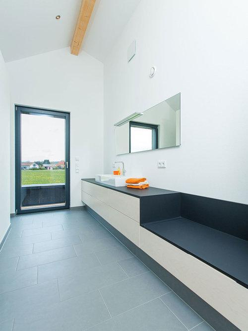 Mittelgroßes Modernes Badezimmer Mit Flächenbündigen Schrankfronten, Hellen  Holzschränken, Grauen Fliesen, Steinplatten, Weißer