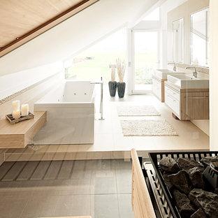 Inredning av ett modernt mellanstort en-suite badrum, med ett fristående handfat, släta luckor, skåp i ljust trä, beige kakel, vita väggar och en jacuzzi