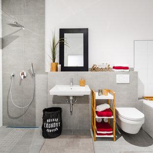 Modernes Badezimmer mit Einbaubadewanne, grauen Fliesen, weißer Wandfarbe, Wandwaschbecken, grauem Boden und Einzelwaschbecken in Köln