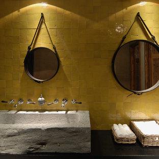 Foto de cuarto de baño rústico con baldosas y/o azulejos amarillos, baldosas y/o azulejos de porcelana, paredes negras y lavabo sobreencimera