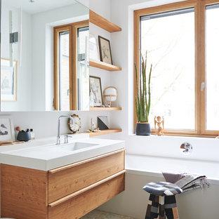 Foto på ett litet skandinaviskt badrum, med ett badkar i en alkov, vita väggar, klinkergolv i småsten, släta luckor, skåp i mellenmörkt trä och ett integrerad handfat