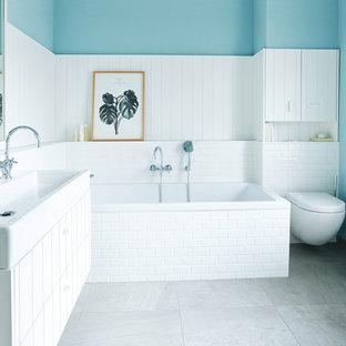 Foto de cuarto de baño de estilo de casa de campo, de tamaño medio, con puertas de armario blancas, bañera encastrada, sanitario de pared, baldosas y/o azulejos de cemento, paredes azules, lavabo sobreencimera y suelo marrón