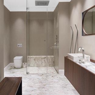 Großes Klassisches Duschbad mit flächenbündigen Schrankfronten, bodengleicher Dusche, Marmorboden, Marmor-Waschbecken/Waschtisch, dunklen Holzschränken, Wandtoilette mit Spülkasten, brauner Wandfarbe, Aufsatzwaschbecken, weißem Boden, Falttür-Duschabtrennung und weißer Waschtischplatte in Hamburg