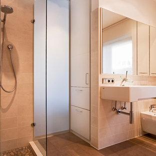 Mittelgroßes Modernes Duschbad mit flächenbündigen Schrankfronten, dunklen Holzschränken, bodengleicher Dusche, Bidet, beigefarbenen Fliesen, weißer Wandfarbe, Wandwaschbecken, braunem Boden und offener Dusche in Berlin