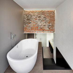 Large urban shower room bathroom in Other with flat-panel cabinets, black cabinets, a freestanding bath, a vessel sink, solid surface worktops and brown floors.