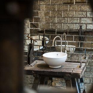 Immagine di una stanza da bagno industriale con vasca freestanding, piastrelle a specchio, pareti bianche, pavimento in cemento, lavabo a bacinella, top in legno, pavimento grigio e top marrone