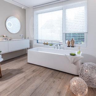 Großes Modernes Duschbad mit flächenbündigen Schrankfronten, weißen Schränken, freistehender Badewanne, weißer Wandfarbe, gebeiztem Holzboden, integriertem Waschbecken und braunem Boden in Düsseldorf