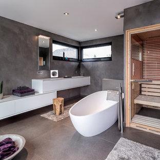 Mittelgroßes Modernes Badezimmer mit flächenbündigen Schrankfronten, weißen Schränken, freistehender Badewanne, bodengleicher Dusche, Wandtoilette, grauen Fliesen, grauer Wandfarbe, Sauna, grauem Boden, Betonboden, Unterbauwaschbecken und Falttür-Duschabtrennung in Düsseldorf