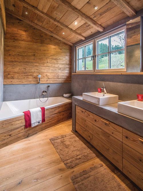 Mittelgroßes Uriges Badezimmer En Suite Mit Flächenbündigen Schrankfronten,  Hellbraunen Holzschränken, Duschbadewanne, Hellem Holzboden