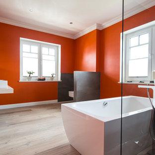 Пример оригинального дизайна: большая ванная комната в современном стиле с отдельно стоящей ванной, душем без бортиков, серой плиткой, оранжевыми стенами, полом из ламината, настольной раковиной, открытым душем, инсталляцией, душевой кабиной и бежевым полом