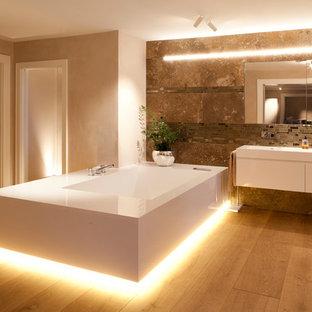 Großes Modernes Badezimmer En Suite mit flächenbündigen Schrankfronten, weißen Schränken, braunen Fliesen, beiger Wandfarbe, braunem Holzboden, freistehender Badewanne, Wandwaschbecken und gelbem Boden in Stuttgart