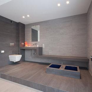 Geräumiges Modernes Badezimmer mit Wandtoilette, grauen Fliesen, Einbaubadewanne, Steinplatten und Einbauwaschbecken in Köln
