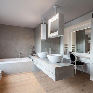 Пример оригинального дизайна: большая главная ванная комната в современном стиле с накладной ванной, серыми стенами, светлым паркетным полом, настольной раковиной, плоскими фасадами, белыми фасадами, столешницей из бетона, инсталляцией, серой плиткой, цементной плиткой и бежевым полом