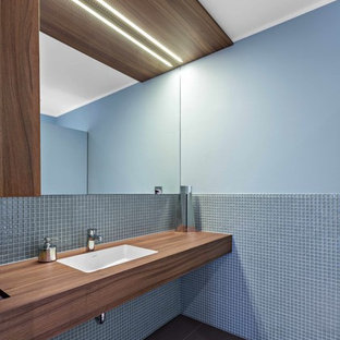 Foto de cuarto de baño moderno con baldosas y/o azulejos azules, baldosas y/o azulejos en mosaico, paredes azules, lavabo bajoencimera, encimera de madera y encimeras marrones