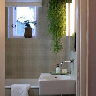 Imagen de cuarto de baño infantil, actual, pequeño, con baldosas y/o azulejos beige, baldosas y/o azulejos en mosaico, lavabo suspendido, bañera encastrada, combinación de ducha y bañera, sanitario de pared, suelo de terrazo, suelo gris y ducha con cortina