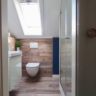 Immagine di una piccola stanza da bagno con doccia con ante bianche, WC sospeso, piastrelle effetto legno, lavabo sospeso e un lavabo