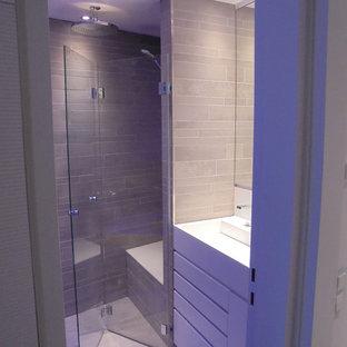 Стильный дизайн: маленькая ванная комната в современном стиле с плоскими фасадами, белыми фасадами, ванной в нише, душем без бортиков, инсталляцией, серой плиткой, керамической плиткой, серыми стенами, полом из керамической плитки, душевой кабиной, монолитной раковиной, столешницей из искусственного камня, серым полом, душем с раздвижными дверями и белой столешницей - последний тренд