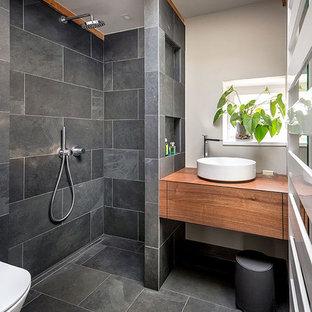 Ejemplo de cuarto de baño con ducha, contemporáneo, pequeño, con puertas de armario de madera en tonos medios, ducha a ras de suelo, sanitario de pared, baldosas y/o azulejos grises, baldosas y/o azulejos de pizarra, paredes grises, suelo de pizarra, lavabo sobreencimera, armarios con paneles lisos, encimera de madera, suelo gris, ducha abierta y encimeras marrones