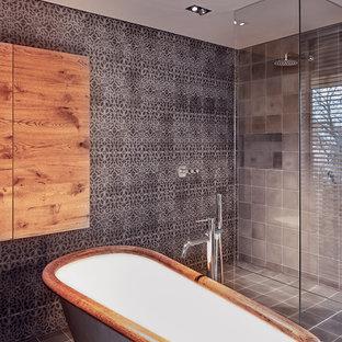 Mittelgroßes Modernes Badezimmer En Suite mit flächenbündigen Schrankfronten, dunklen Holzschränken, freistehender Badewanne, bodengleicher Dusche, Wandtoilette, grauen Fliesen, beiger Wandfarbe, Aufsatzwaschbecken, Waschtisch aus Holz, grauem Boden, offener Dusche und Kalkfliesen in Berlin