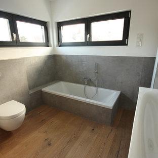 Inspiration för ett funkis badrum, med en kantlös dusch, grå kakel, bänkskiva i glas och grått golv