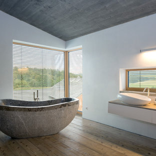 Inspiration for a large contemporary medium tone wood floor, brown floor, single-sink and shiplap ceiling freestanding bathtub remodel in Munich with flat-panel cabinets, white cabinets, white walls, a vessel sink, wood countertops, brown countertops and a floating vanity