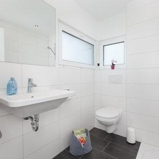Kleines Skandinavisches Duschbad mit Wandtoilette, weißen Fliesen, Keramikfliesen, weißer Wandfarbe, Wandwaschbecken, schwarzem Boden und offener Dusche in Stuttgart
