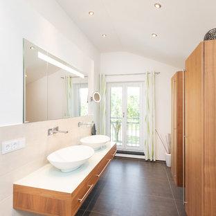 Kleines Modernes Badezimmer En Suite mit flächenbündigen Schrankfronten, hellbraunen Holzschränken, beigefarbenen Fliesen, Keramikfliesen, weißer Wandfarbe, Porzellan-Bodenfliesen, Aufsatzwaschbecken, Waschtisch aus Holz, grauem Boden und weißer Waschtischplatte in Nürnberg