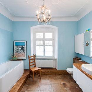 Новый формат декора квартиры: ванная комната среднего размера в стиле кантри с белыми фасадами, инсталляцией, коричневой плиткой, синими стенами, полом из терракотовой плитки, столешницей из дерева, коричневым полом, коричневой столешницей, плоскими фасадами, ванной в нише, угловым душем, накладной раковиной и душем с распашными дверями