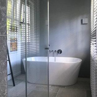 Esempio di una stanza da bagno con doccia moderna di medie dimensioni con vasca freestanding, doccia a filo pavimento, pareti grigie, pavimento grigio e porta doccia scorrevole