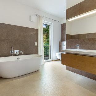 Mittelgroßes Modernes Badezimmer En Suite mit flächenbündigen Schrankfronten, hellbraunen Holzschränken, freistehender Badewanne, Toilette mit Aufsatzspülkasten, beigefarbenen Fliesen, Steinfliesen, Kalkstein, brauner Wandfarbe und integriertem Waschbecken in Köln