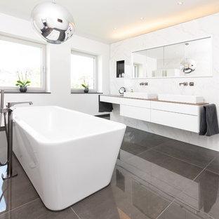 Großes Modernes Badezimmer En Suite mit flächenbündigen Schrankfronten, weißen Schränken, freistehender Badewanne, weißer Wandfarbe, Porzellan-Bodenfliesen, Aufsatzwaschbecken, Waschtisch aus Holz, grauem Boden und brauner Waschtischplatte in Nürnberg