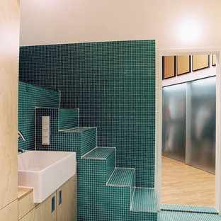 Photo of a medium sized mediterranean bathroom in Berlin with flat-panel cabinets, light wood cabinets, green tiles, white walls, mosaic tile flooring, a vessel sink, wooden worktops and green floors.
