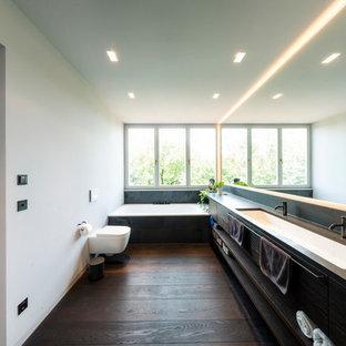 Geräumiges Modernes Duschbad mit flächenbündigen Schrankfronten, Einbaubadewanne, Wandtoilette, grauer Wandfarbe, braunem Holzboden, Mineralwerkstoff-Waschtisch, braunem Boden, dunklen Holzschränken, schwarzen Fliesen, integriertem Waschbecken und brauner Waschtischplatte in München
