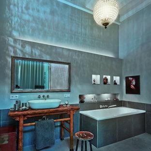 Großes Asiatisches Duschbad mit Einbaubadewanne, schwarzen Fliesen, Zementfliesen, grauer Wandfarbe, Betonboden, Aufsatzwaschbecken, Waschtisch aus Holz, grauem Boden und brauner Waschtischplatte in Berlin