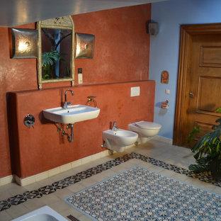 Immagine di un'ampia stanza da bagno padronale mediterranea con piastrelle di cemento, vasca giapponese, doccia a filo pavimento, bidè, piastrelle multicolore, pareti rosse, pavimento con piastrelle a mosaico e lavabo sospeso