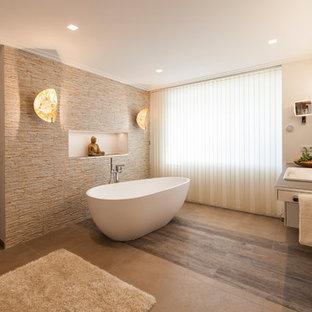 Удачное сочетание для дизайна помещения: главная ванная комната среднего размера в восточном стиле с отдельно стоящей ванной, бежевой плиткой, бежевыми стенами, накладной раковиной, бежевым полом, плоскими фасадами, белыми фасадами и каменной плиткой - самое интересное для вас