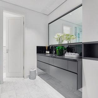 Mittelgroßes Modernes Badezimmer mit flächenbündigen Schrankfronten, grauen Schränken, weißer Wandfarbe, Marmorboden, integriertem Waschbecken, weißem Boden und grauer Waschtischplatte in Berlin