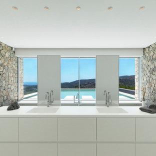 Foto de cuarto de baño principal, actual, grande, con armarios con paneles lisos, puertas de armario blancas, paredes grises, lavabo integrado, suelo blanco y encimeras blancas