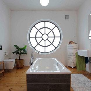 Mittelgroßes Klassisches Badezimmer En Suite mit Einbaubadewanne, Wandtoilette, weißer Wandfarbe, braunem Holzboden, Wandwaschbecken, braunem Boden, weißen Fliesen und Keramikfliesen in Dortmund
