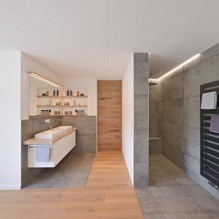 Inredning av ett modernt stort badrum med dusch, med släta luckor, vita skåp, en kantlös dusch, svart kakel, stenhäll, vita väggar, mellanmörkt trägolv, ett fristående handfat, träbänkskiva och med dusch som är öppen