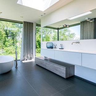 Großes Modernes Badezimmer En Suite mit flächenbündigen Schrankfronten, freistehender Badewanne, weißer Wandfarbe, integriertem Waschbecken, schwarzem Boden, weißer Waschtischplatte und weißen Schränken in München