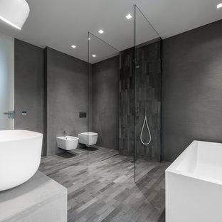 Foto de cuarto de baño con ducha, moderno, grande, con bañera exenta, ducha a ras de suelo, sanitario de pared, baldosas y/o azulejos grises, paredes grises, lavabo sobreencimera, encimera de cemento, suelo gris, ducha abierta, puertas de armario grises, azulejos en listel, suelo de cemento y encimeras grises