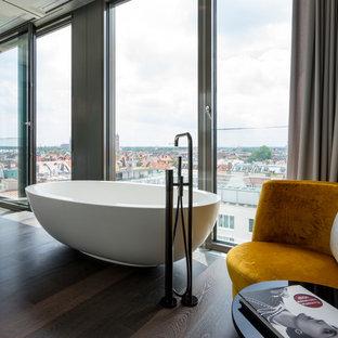 Großes Modernes Badezimmer En Suite mit freistehender Badewanne, dunklem Holzboden und braunem Boden in München