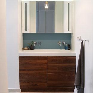 Ejemplo de cuarto de baño principal, contemporáneo, de tamaño medio, con armarios con paneles lisos, puertas de armario de madera en tonos medios, bañera encastrada, sanitario de pared, baldosas y/o azulejos beige, paredes azules, suelo de bambú, lavabo tipo consola, encimera de acrílico y suelo blanco