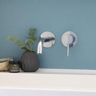 Ejemplo de cuarto de baño principal, actual, de tamaño medio, con armarios con paneles lisos, puertas de armario de madera en tonos medios, bañera encastrada, sanitario de pared, suelo de bambú, lavabo tipo consola, encimera de acrílico y suelo blanco
