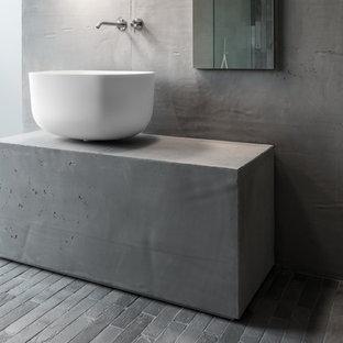 Foto di una stanza da bagno moderna di medie dimensioni con ante di vetro, pareti grigie, top in cemento, pavimento grigio, lavabo a bacinella e top grigio