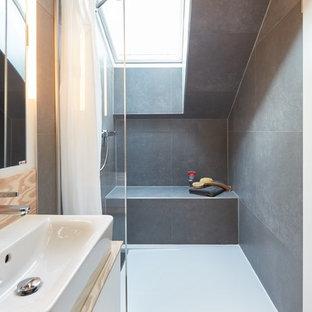 Modelo de cuarto de baño con ducha, contemporáneo, pequeño, con puertas de armario blancas, ducha abierta, sanitario de pared, baldosas y/o azulejos grises, baldosas y/o azulejos de piedra, paredes grises, suelo de madera clara, lavabo suspendido, suelo blanco, ducha con cortina y encimeras beige