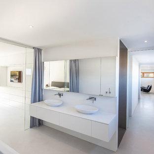 Modernes Badezimmer mit flächenbündigen Schrankfronten, weißen Schränken, weißer Wandfarbe, Betonboden, Aufsatzwaschbecken, grauem Boden und weißer Waschtischplatte in Sonstige